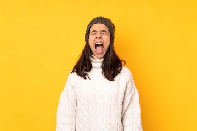 Młoda kobieta z zimowym kapeluszem na białym tle krzycząc do przodu z szeroko otwartymi ustami
