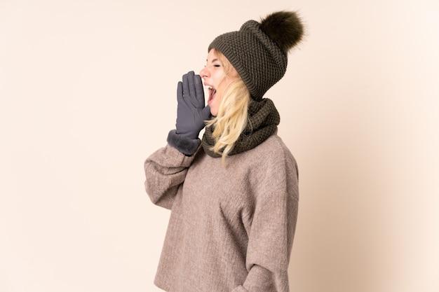 Młoda kobieta z zimowym kapeluszem na odizolowanej ścianie krzycząc z szeroko otwartymi ustami