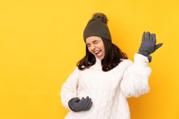 Młoda kobieta z zimowym kapeluszem na odosobnionym żółtym tle robi gitara gestowi