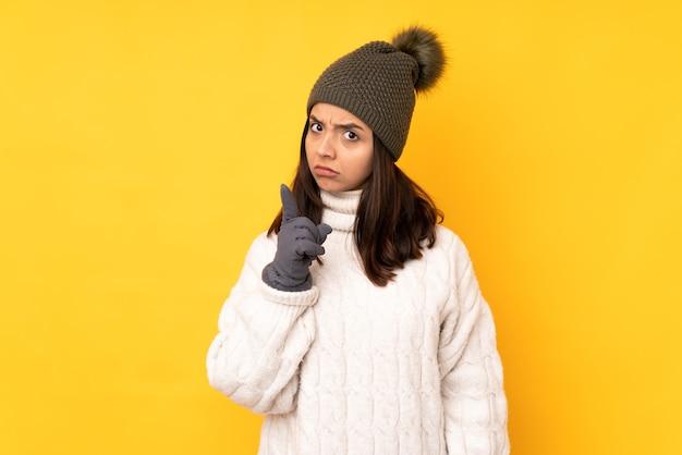 Młoda kobieta z zimowym kapeluszem na żółtym sfrustrowana i wskazująca na przód