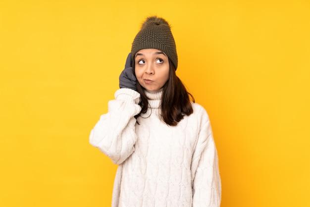 Młoda kobieta z zimowym kapeluszem nad odosobnioną kolor żółty ścianą myśleć pomysł