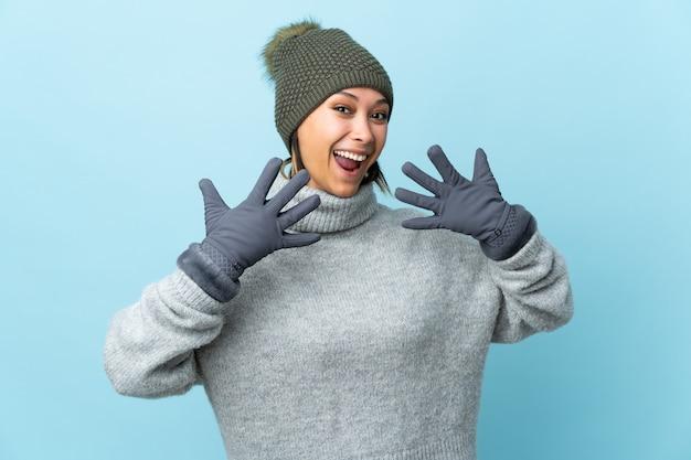 Młoda kobieta z zimowym kapeluszem odizolowywającym na błękit przestrzeni z niespodzianka wyrazem twarzy