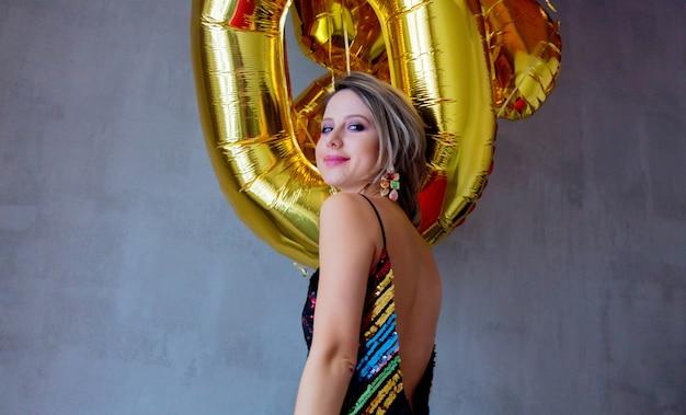 Młoda kobieta z złote balony na jej urodziny trzydzieści lat. osoba jest w sukience i fryzurze w stylu vintage z lat 80-tych. na szarym tle