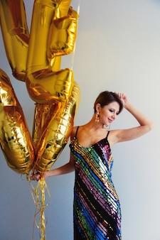 Młoda kobieta z złote balony na jej urodziny trzydzieści lat. osoba jest w sukience i fryzurze w stylu vintage z lat 80-tych. w domu