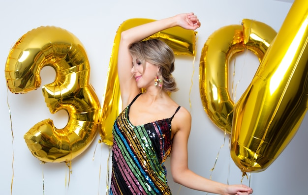 Młoda kobieta z złote balony na jej urodziny trzydzieści lat. osoba jest w sukience i fryzurze w stylu vintage z lat 80-tych.