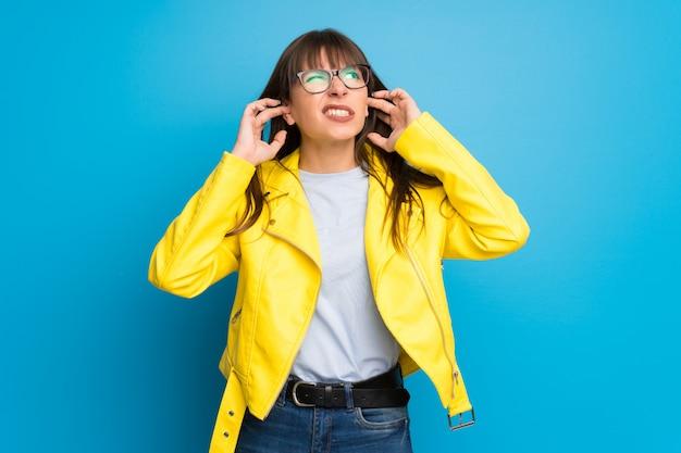 Młoda kobieta z żółtą kurtką zakrywa ucho z rękami. sfrustrowany wyraz