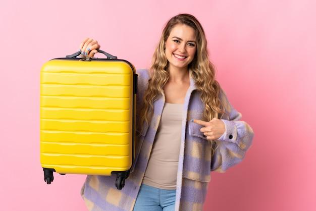 Młoda kobieta z żółtą podróżną walizką