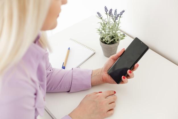 Młoda kobieta za pomocą aplikacji na smartfonie z ekranem dotykowym. koncepcja korzystania z technologii, robienia zakupów online, aplikacji mobilnych, sms-ów, uzależnienia, przesuń w górę, przesuń w dół.