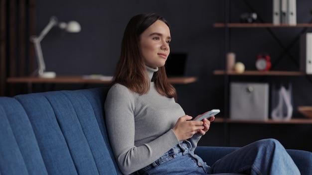 Młoda kobieta za pomocą aplikacji na telefon komórkowy