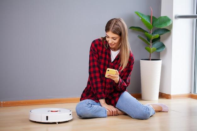 Młoda kobieta za pomocą automatycznego odkurzacza do czyszczenia podłogi.
