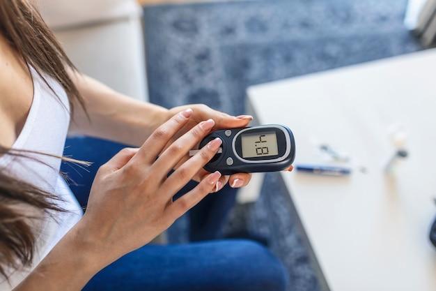 Młoda kobieta za pomocą cyfrowego glukometru w domu. kontrola cukrzycy
