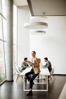 Młoda kobieta za pomocą cyfrowego tabletu przed swoim zespołem w nowoczesnym biurze