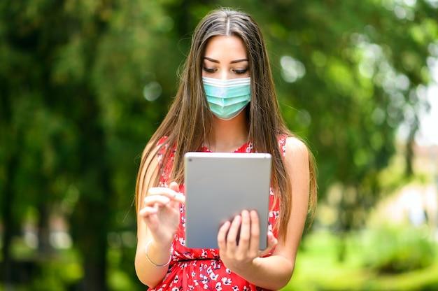 Młoda kobieta za pomocą cyfrowego tabletu siedzi na ławce w parku i nosi maskę, koncepcja koronawirusa