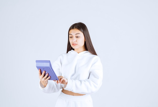 Młoda kobieta za pomocą kalkulatora na biało szarym tle.