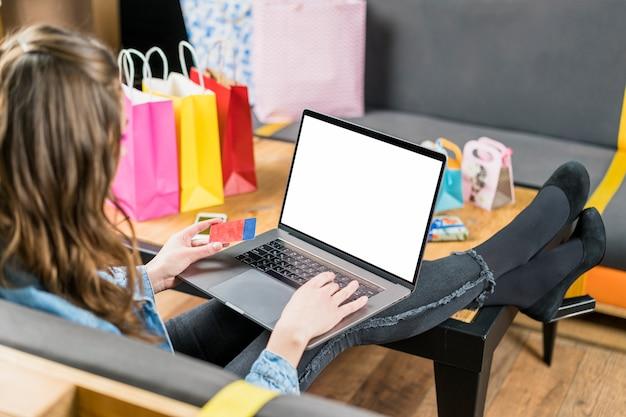 Młoda kobieta za pomocą karty kredytowej do płatności zakupów online na laptopie