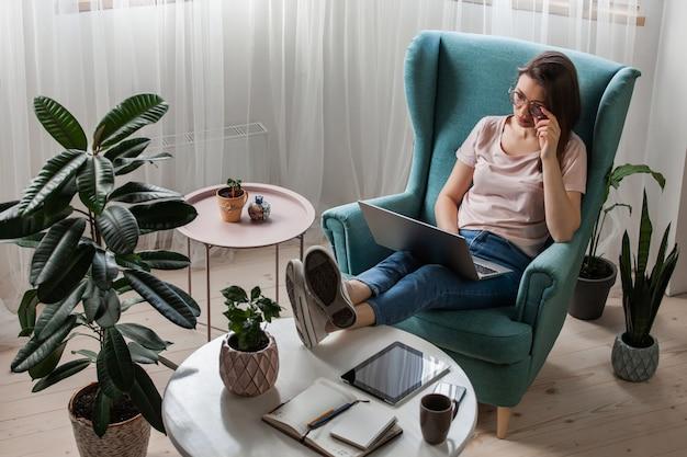 Młoda kobieta za pomocą laptopa do pracy w domu