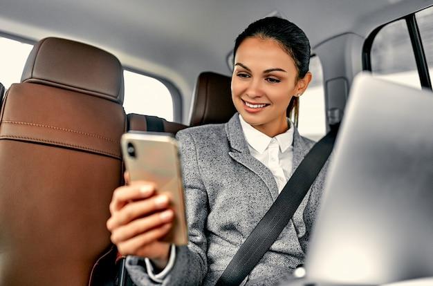 Młoda kobieta za pomocą laptopa i telefonu na tylnym siedzeniu w samochodzie. kobieta executive podróżująca do pracy w luksusowym samochodzie.