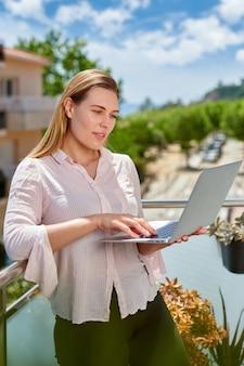 Młoda kobieta za pomocą laptopa na balkonie. wakacje w koncepcji ośrodka.
