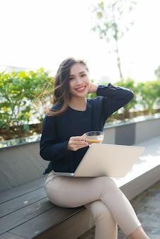 Młoda kobieta za pomocą laptopa. piękna dziewczyna pracuje na laptopie na świeżym powietrzu