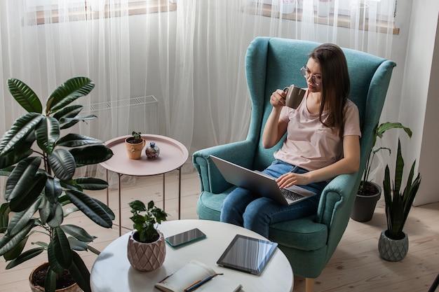 Młoda kobieta za pomocą laptopa, pracy w domu i picia kawy