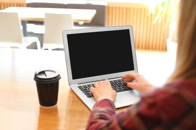 Młoda kobieta za pomocą laptopa przy stole w kawiarni