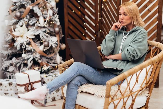 Młoda kobieta za pomocą laptopa siedząc na krześle w domu.