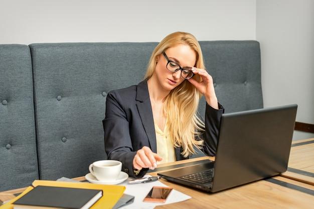 Młoda kobieta za pomocą laptopa siedząc przy stole w kawiarni