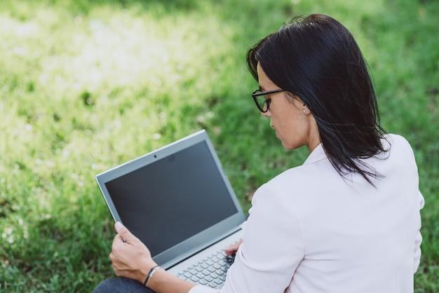 Młoda kobieta za pomocą laptopa z pustym ekranem w parku podczas pracy na świeżym powietrzu.