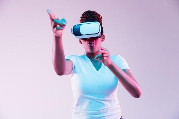 Młoda kobieta za pomocą okularów vr w świetle neonu