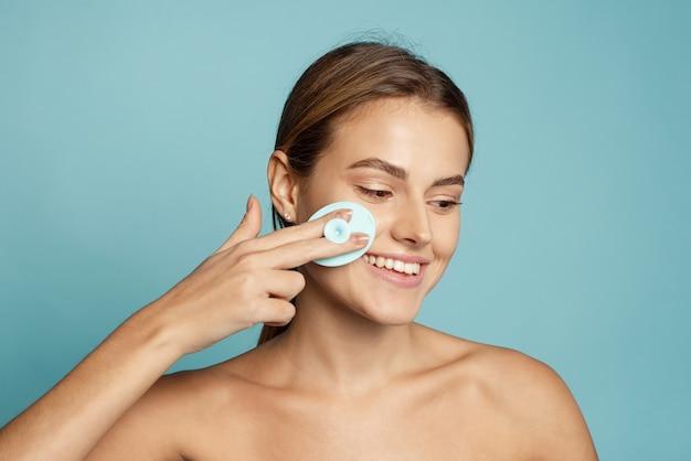 Młoda kobieta za pomocą silikonowej szczoteczki do oczyszczania twarzy na niebieskim tle.