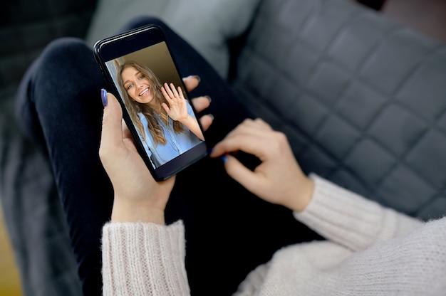 Młoda kobieta za pomocą smartfona do połączenia wideo. wysokiej jakości zdjęcie
