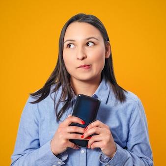 Młoda kobieta za pomocą smartfona i uśmiechnięty. na żółtym tle.
