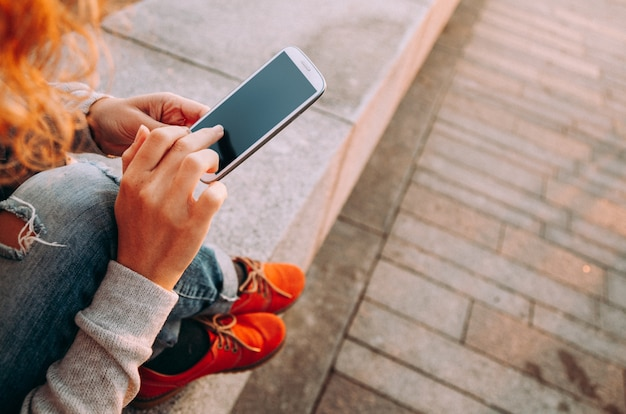 Młoda kobieta za pomocą smartfona na zewnątrz o zachodzie słońca