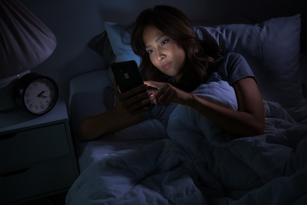 Młoda kobieta za pomocą smartfona w łóżku w nocy