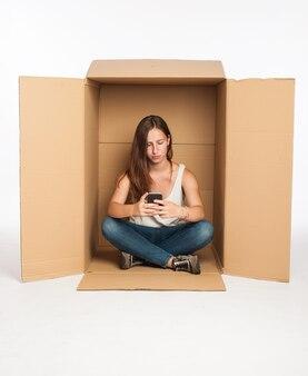 Młoda kobieta za pomocą smartfona wewnątrz pudełka