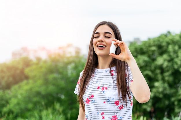 Młoda kobieta za pomocą sprayu do nosa dla alergii na pyłki i trawę