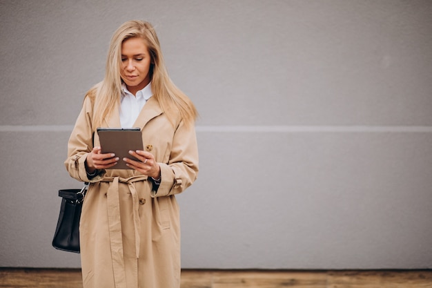 Młoda kobieta za pomocą tabletu przy ścianie poza ulicą