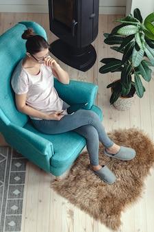 Młoda kobieta za pomocą tabletu, siedząc w wygodnym fotelu