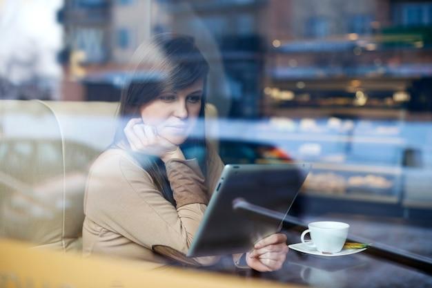 Młoda kobieta za pomocą tabletu w kawiarni