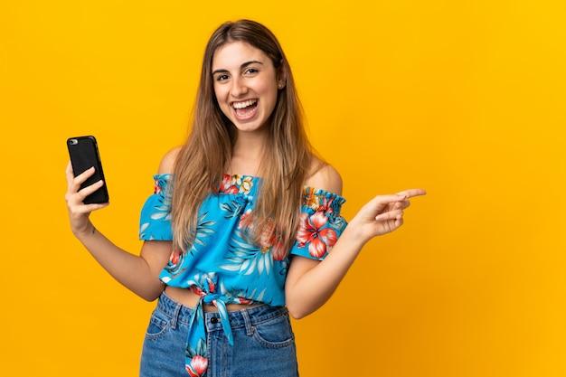 Młoda kobieta za pomocą telefonu komórkowego na na białym tle żółty zaskoczony i wskazujący palec na bok