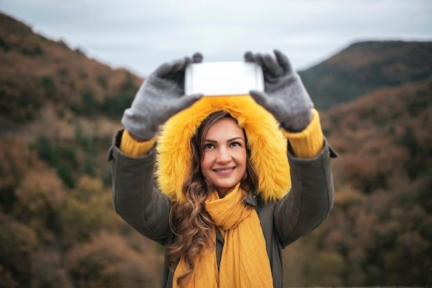 Młoda kobieta za pomocą telefonu komórkowego w lesie. koncepcja mobilna.