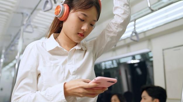 Młoda kobieta za pomocą telefonu komórkowego w pociągu publicznym