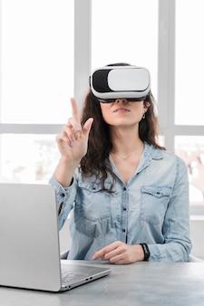 Młoda kobieta za pomocą zestawu słuchawkowego wirtualnej rzeczywistości