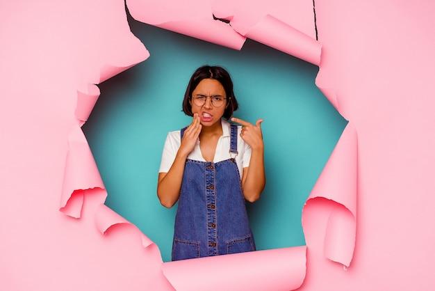 Młoda kobieta za złamaną ścianą z bólem zęba