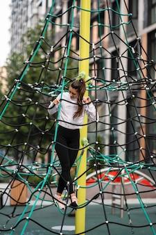 Młoda kobieta, zabawy na piramidzie liny na placu zabaw