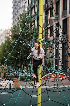 Młoda kobieta, zabawy na piramidzie liny