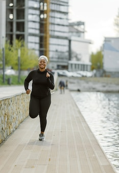 Młoda kobieta zabawy szkolenia na świeżym powietrzu. koncepcja życia sportowego ludzi. kobieta w sportowej joggingu