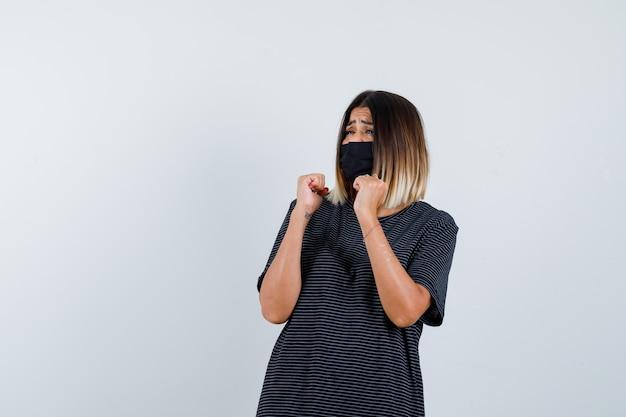Młoda kobieta zaciskająca pięści w czarnej sukience, czarnej masce i wyglądająca na przestraszoną, widok z przodu.