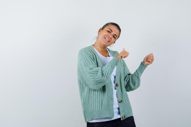 Młoda kobieta zaciskająca pięści, wskazująca w prawo w białej koszuli i miętowozielonym swetrze i wyglądająca na szczęśliwą