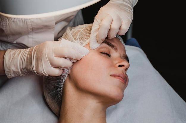 Młoda kobieta zaczyna zabieg kosmetyczny w centrum odnowy biologicznej